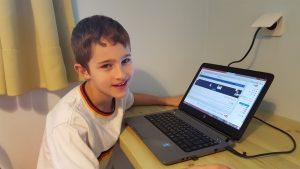 למידה מרחוק ילד בחולצה לבנה ליד המחשב שלו- כל הזכויות שמורות ללחישות לילה להעצמת ילדים
